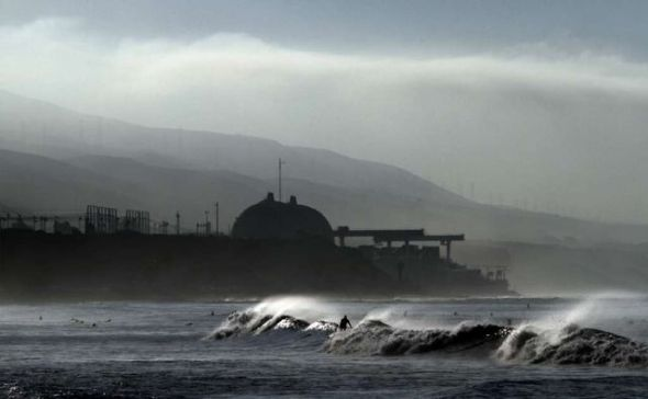 Surfers work the waves at Lower Trestles near San Clemente while the darkened San Onofre nuclear plant rises up in the background. Photo by Mark Boster, Los Angeles Times