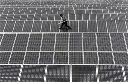 A worker in China scampers along a solar array. Photo courtesy of WikimediaCommons.