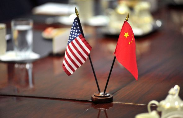 The American and Chinese flags stand at center table before a meeting between U.S. and Chinese delegates for a meeting at the Pentagon, from Aug. 23, 2012. This Image was released by the United States Department of Defense. Photo by Glenn Fawcett, courtesy of WikimediaCommons.