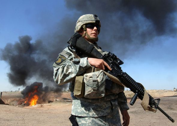 U.S. Army Staff Sgt. Darren Vogt, assigned the 1st Battalion 66th Armor Regiment, performs perimeter security in an area where a recent insurgent attack took place on an Iraqi oil pipeline near Taji. U.S. Navy photo by Photographer's Mate 1st Class Michael Larson from March 11, 2006, courtesy of WikimediaCommons.